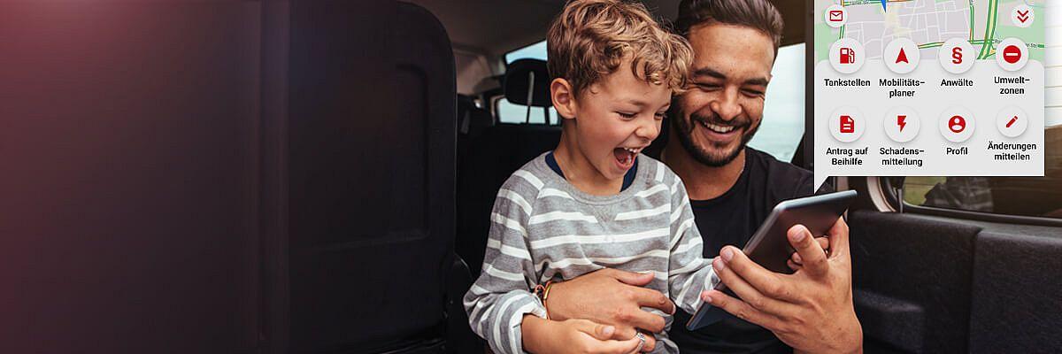 Vater mit Sohn schaut auf dem Handy die App an