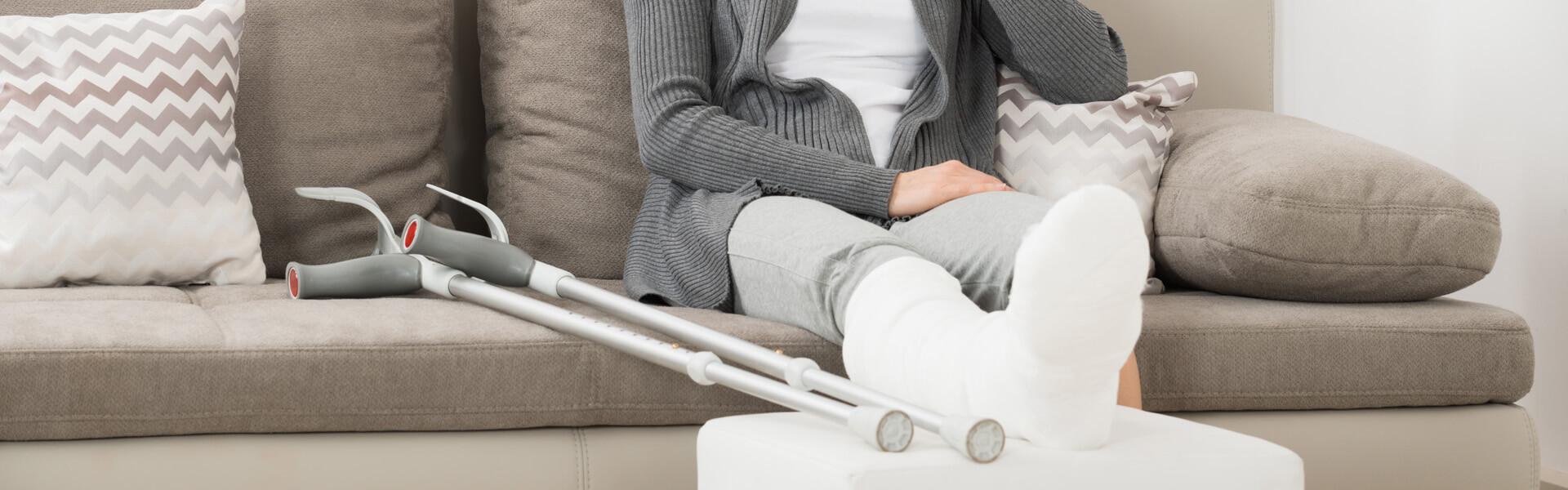Frau mit gebrochenem Bein in Gips und Krücken sitzt auf dem Sofa.