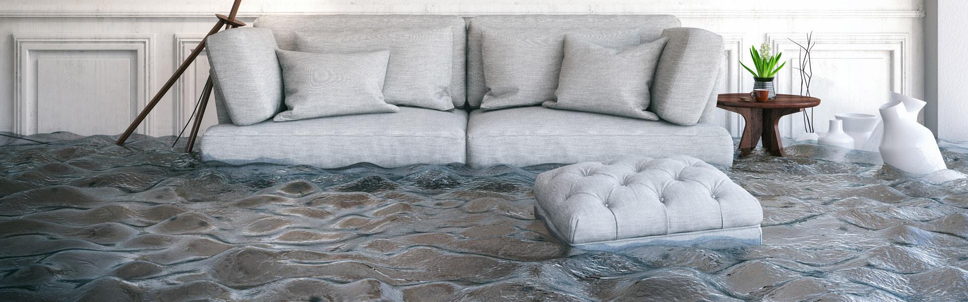 Durch Wasser beschädigter Hausrat: Couch, Lampe, Tisch