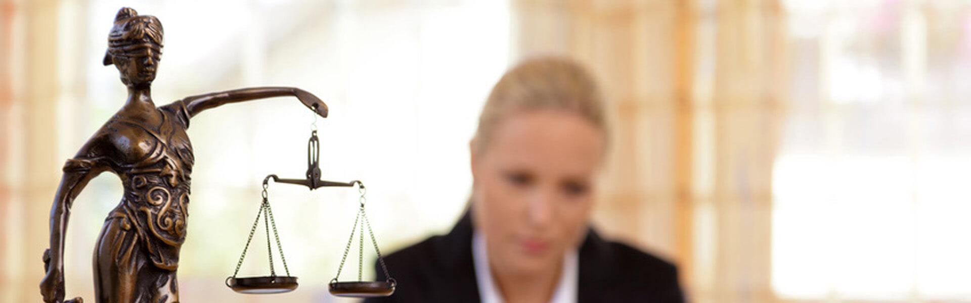 Anwältin sitzt am Schreibtisch, vor sich eine Statue der Justizia